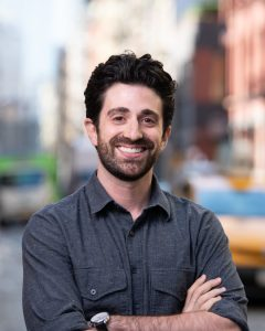 Photo of the author standing with crossed arms and smiling, with an urban background.