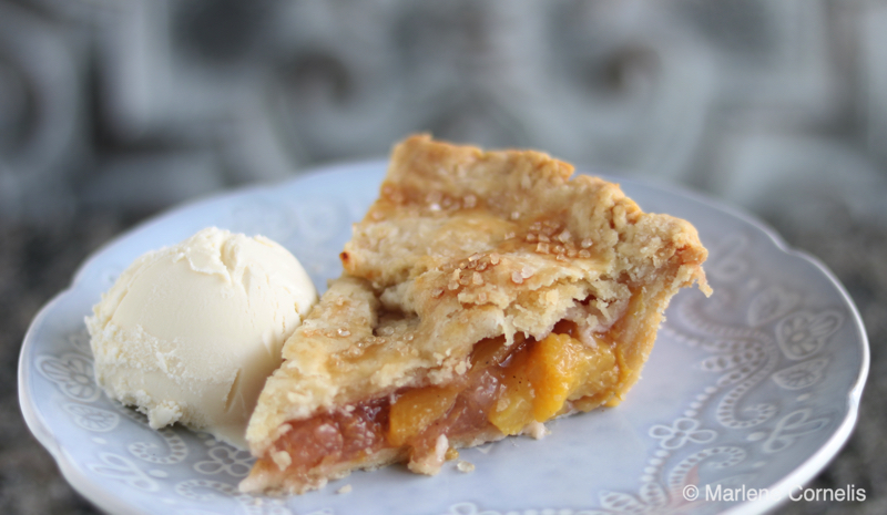 A slice of peach pie with a scoop of vanilla ice cream on a pale blue plate.